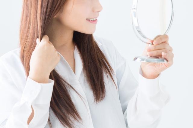 髪の毛を触りながら鏡を見て微笑む女性